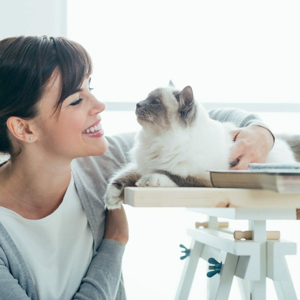 Happy woman cuddling her cat
