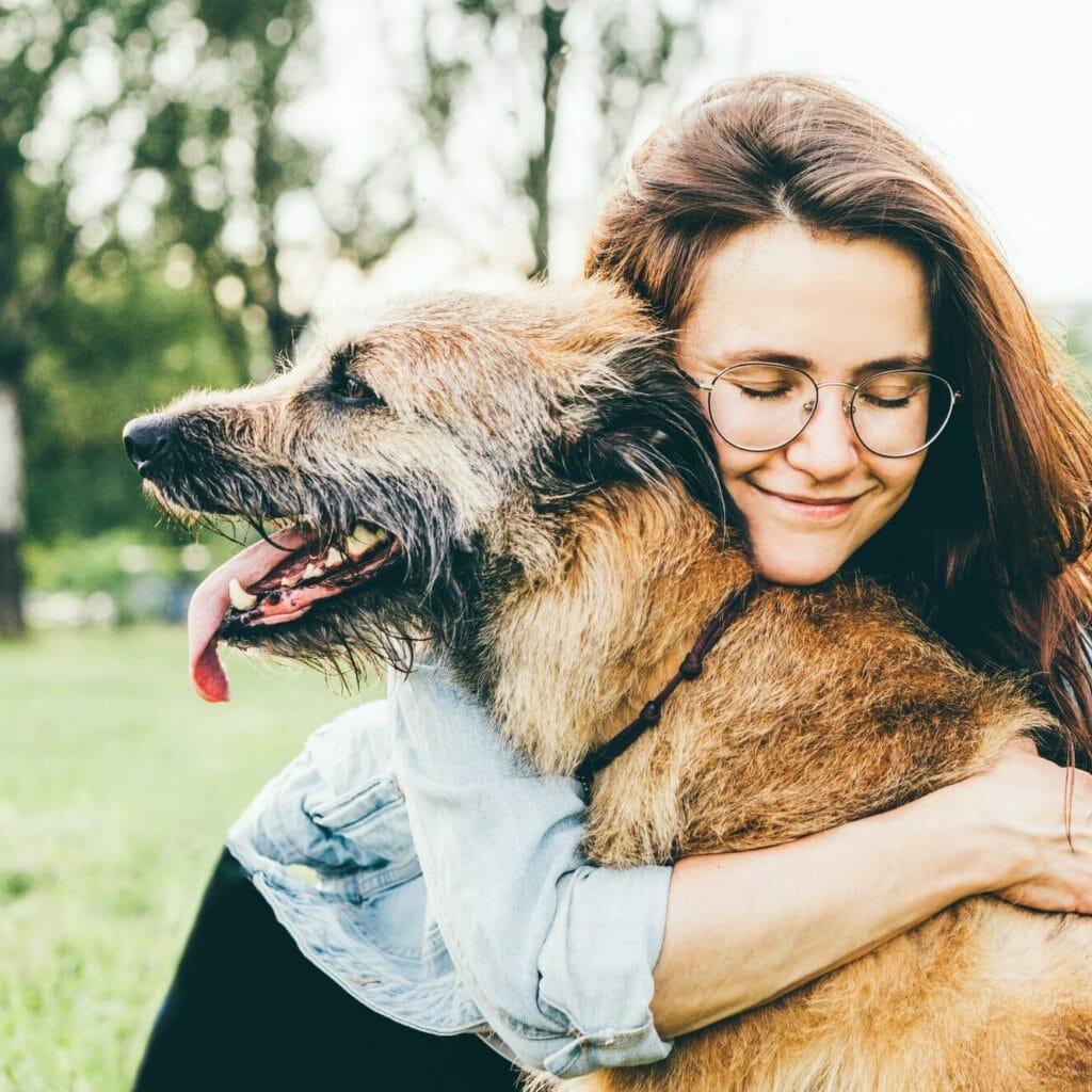 Women hugging dog in the summer park.